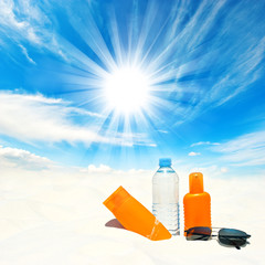 Sunscreen cream and bottle of water over sunny blue sky
