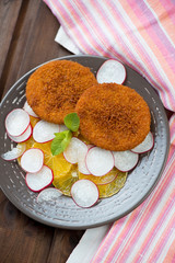Roasted salmon cakes with sliced oranges and radish, above view