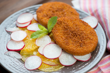 Close-up of roasted fish burgers with oranges and radish
