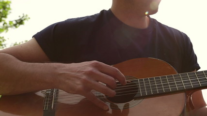 Attractive man playing a guitar in the sunlight