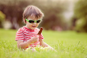 Cute kid with sunglasses, eating chocolate lollipops at the park