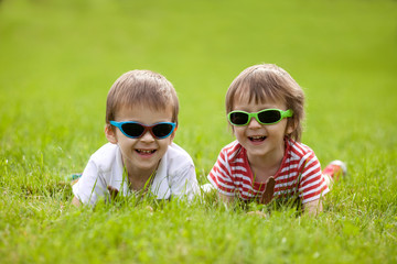 Cute kids with sunglasses, eating chocolate lollipops at the par