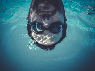 funny man swimming underwater in a pool