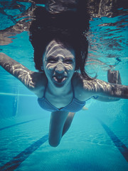 smiling, teenager diving into a pool