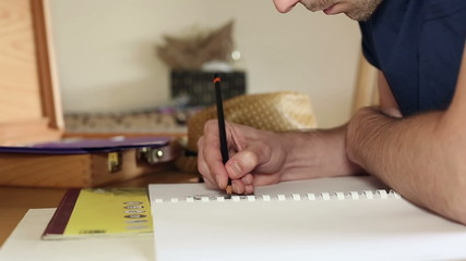 Attractive artist concentrating whilst he draws