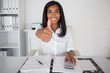 Pretty businesswoman showing thumb up to camera at her desk