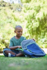Happy schoolboy opening his schoolbag sitting on grass