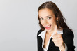 Businesswoman with thumbs up, over grey