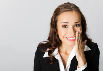 Business woman covering mouth, over grey