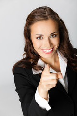 Business woman pointing finger at viewer, over grey