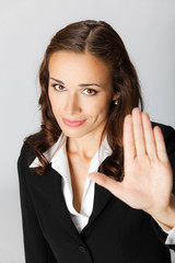Businesswoman with stop gesture, over grey