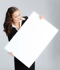Businesswoman showing signboard, over grey