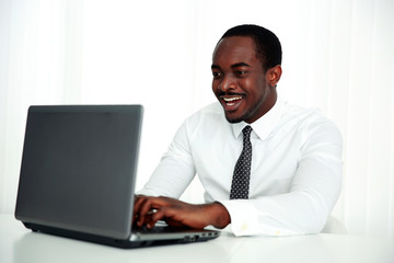 Laughing african man using laptop in office