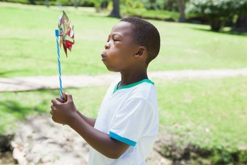 Little boy blowing pinwheel in the park