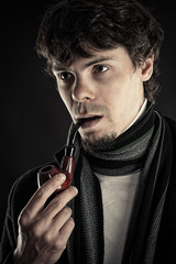 intelligent man with a pipe in a mouth isolated on black