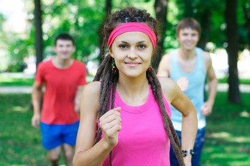 Smiling girl jogging with two guys on the background at the park