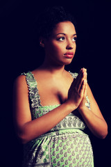 Young afro american pregnant woman praying