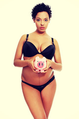Pregnant woman holding a pink piggybank