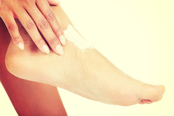 Female hands treating feet with moisturizing cream