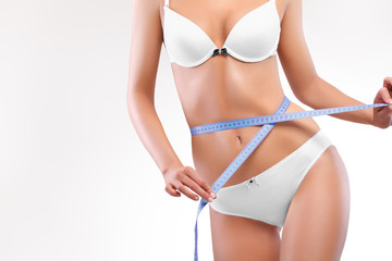 Slim Woman Body in Panties with Measure on white background