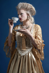 Retro baroque fashion woman wearing gold dress. Holding a cup of