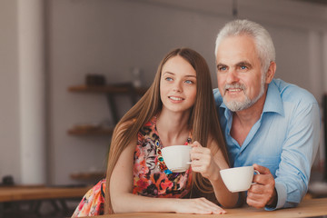 senior man with drinking cofee with beautiful woman