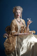 Retro baroque fashion woman wearing gold dress. Holding wine gla