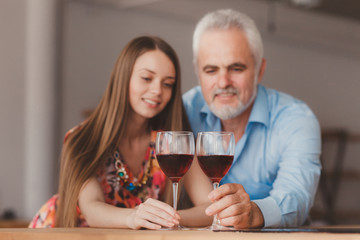 young girl and senior man holding wine glasess