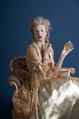 Retro baroque fashion woman wearing gold dress. Holding bottle o