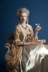 Retro baroque fashion woman wearing gold dress. Holding wine gla