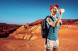 Portrait of drinking traveler with backpack in the desert.