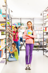 Girl with notebook stands in library near shelves
