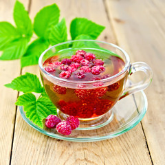 Tea with raspberries in glass cup on board