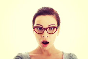 Young casual woman in eyeglasses expresses shock.