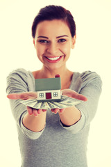 Young beautiful woman with money and house .
