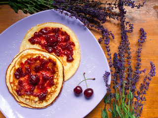 Delicious pancakes on a table surrounded by purple flowers