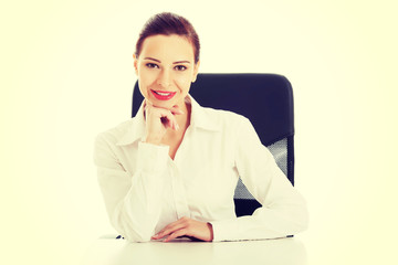 Beautiful business woman, boss sitting on a chair.