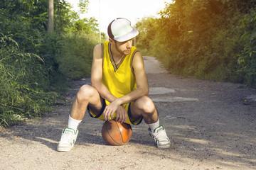 Young basketball player sitting on ball