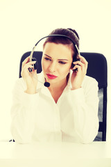 Woman sitting with microphone and headphones.