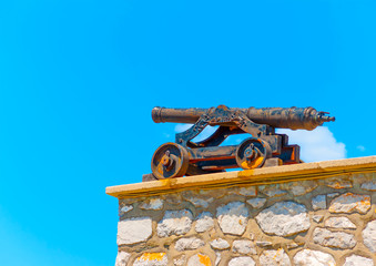 Old cannons over the historic port of Hydra island in Greece