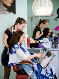 Happy young woman getting a new haircut by hairdresser at parlor poster