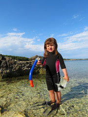 Portrait of happy girl with wetsuit, masks and snorkels at the s