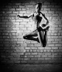Muscular jumping woman on brick wall (monochrome version)