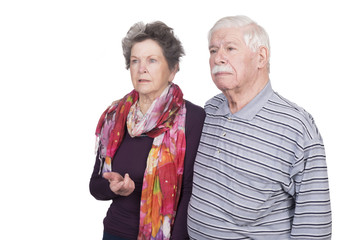 Elderly couple standing with expressions