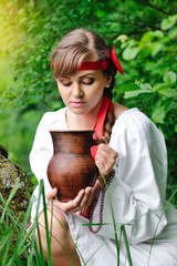 Beautiful young girl with a ceramic jug at the well