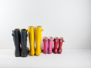 rubber boots against a white wall