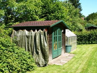 Gemähter Rasen mit Gartenhütte und Gewächshaus in Lippe