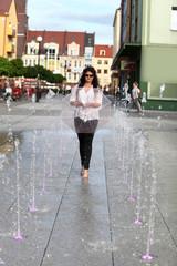 Dziewczyna z parasolką w fontannie.