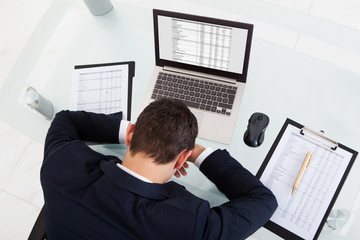 Tired Businessman Sleeping While Calculating Expenses In Office