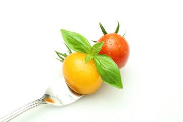 フォークに刺さったミニトマトとバジル